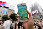 """A man poses with his mobile phone displaying the augmented reality mobile game """"Pokemon Go"""" by Nintendo in front of a busy crossing in Shibuya district in Tokyo, Japan, July 22, 2016. REUTERS/Toru Hanai"""