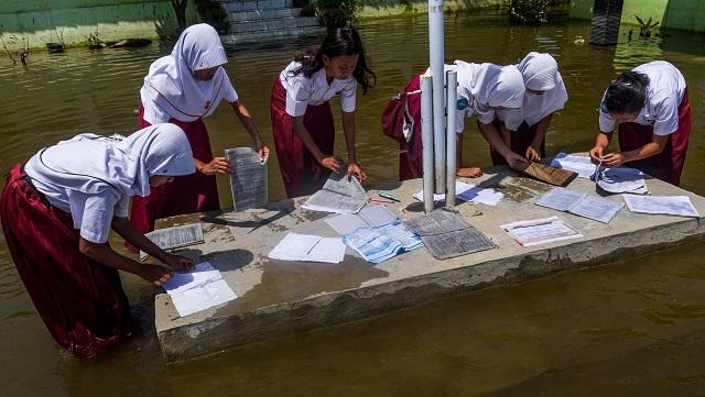Sejumlah siswa menjemur buku yang masih bisa diselamatkan dari rendaman banjir yang melanda SD Negeri Sayung 1 Demak, Jawa Tengah, Senin (20/2). Meski banjir berangsur surut namun sejumlah ruang kelas di sekolah itu masih tergenang air. Untuk sementara kegiatan belajar mengajar dipindahkan ke ruang yang sudah tidak terendam. ANTARA FOTO/Aji Styawan/tom/kye/17.